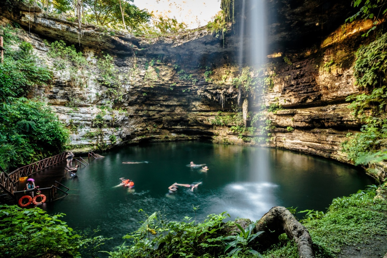 personas nadando en el cenote saamal